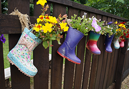 Wellies on a fence with plants in them